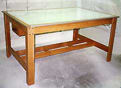 Photo of fixed top, four poster light table with drawer.